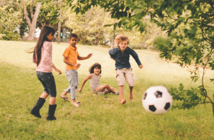 Children playing with a football in in a field