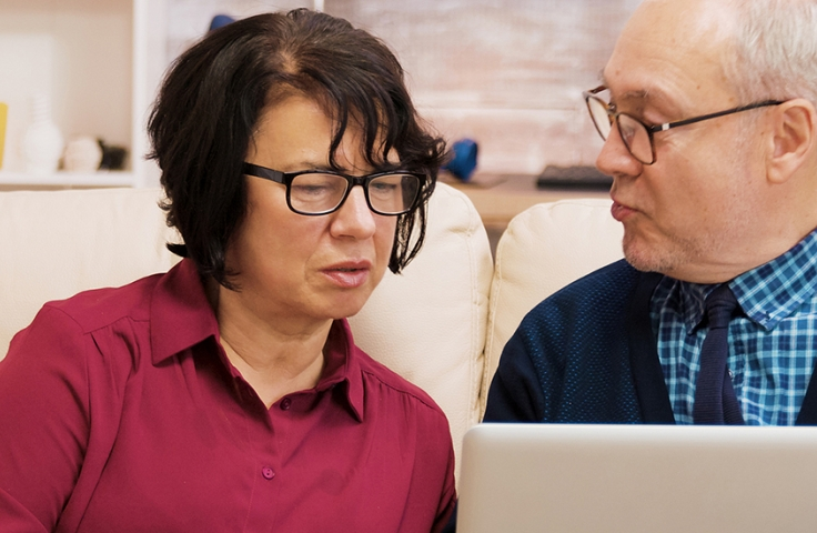 Older couple sitting on sofa looking at laptop
